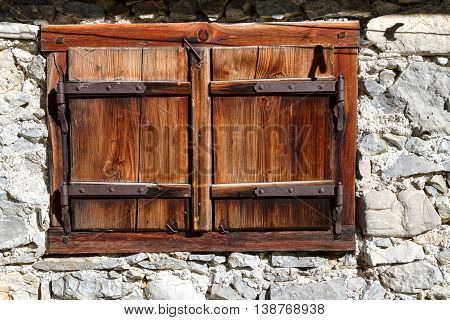 Closed vintage window on stone wall a house. Outdoors alpine scene Austria Tyrol.
