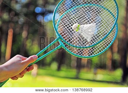 Hand holding the green badminton rackets outdoors