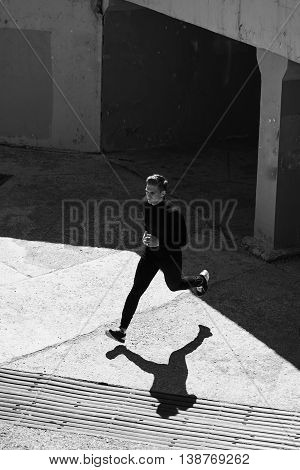 Black-and-white photo of an athlete running in the wall of the city
