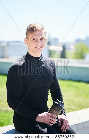 Portrait of an athlete men in black tight clothes with a shaker in hand sitting on city background