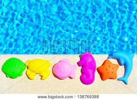 Baby Toys on the blue pool background.