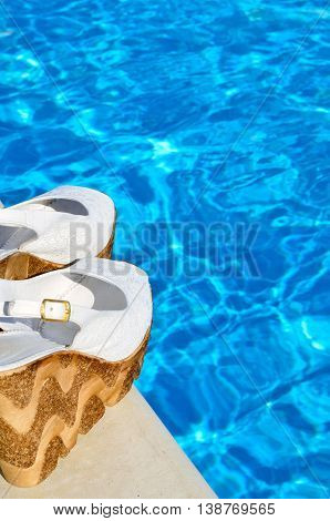 Women's white sandals on the pool background.