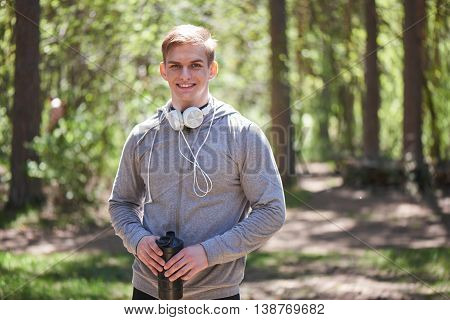 Portrait of a smiling athlete with headphones around his neck holding the shaker in hand on a forest background