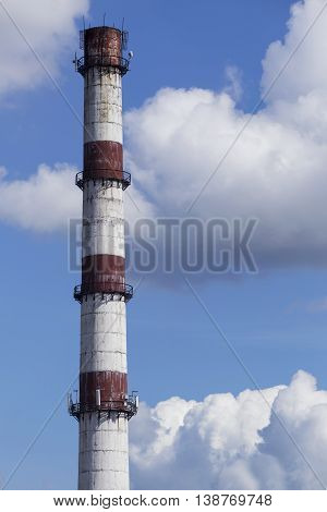 Industrial chimney against the sky with clouds