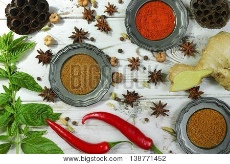 Colorful variety of Indian spices on white wooden table top