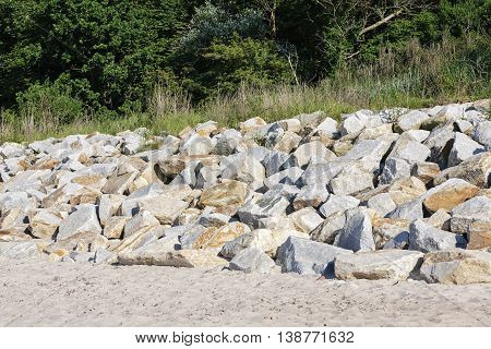 Boulders on the beach placed to protect the dunes from the ravages of the sea waves by the Baltic Sea in Kolobrzeg