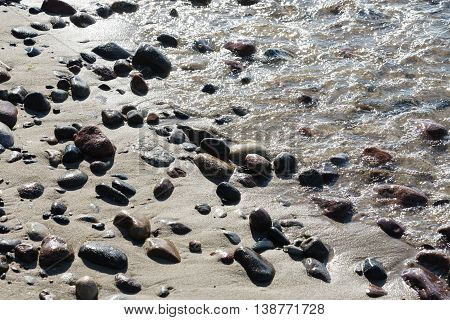 Stones on a sandy beach at the coastline of the Baltic Sea in the back light in Kolobrzeg in Poland