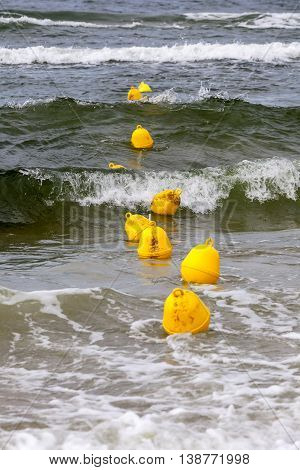 Yellow buoys on the surface of the sea of Baltic define the boundary of the safe swimming at the beach in Kolobrzeg in Poland