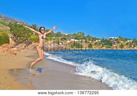 happy woman jumping at a greek beach - greek summer photos