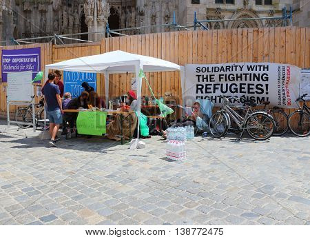 REGENSBURG GERMANY - JUNE 9, 2016: Unidentified activists protesting against deportation of refugees of Germany. Political propaganda on Regensburg square.