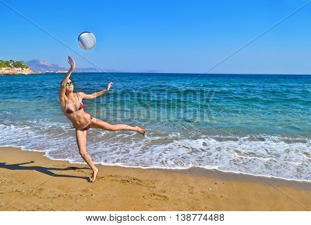 woman playing volleyball at a greek beach - greek summer photo