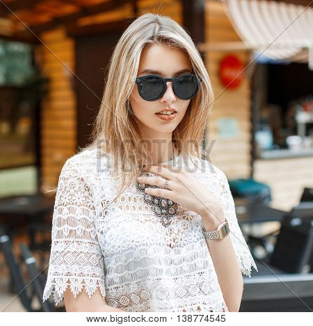 Stylish Pretty Woman In White Lace Blouse And Sunglasses Posing On The Background Of Summer Cafe In