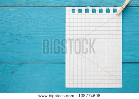 A piece of paper with a pin on turquoise blue wooden Board