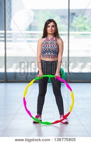 Young woman with hula loop in gym in health concept