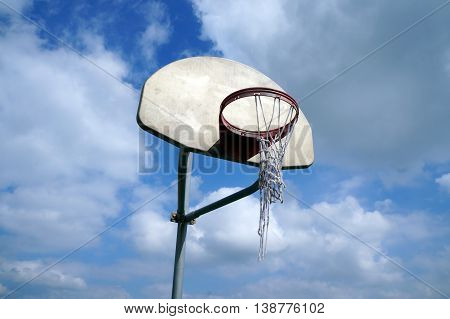A basketball hoop with a torn net, against a blue sky with white clouds, in Shorewood, Illinois.
