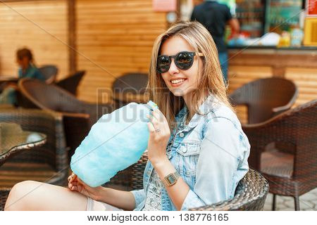 Cheerful Young Pretty Girl With A Smile Eats Cotton Candy On A Sunny Day.