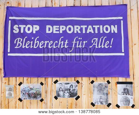 REGENSBURG GERMANY - JUNE 9, 2016: Poster with protest against deportation of refugees of germany. Political propaganda on board-fence.
