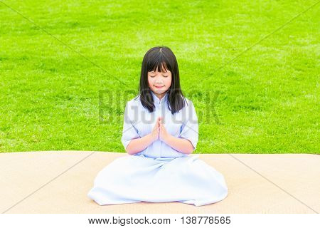 Close up of beautiful buddhist asian girl sit on wooden mat praying and meditation in the garden.