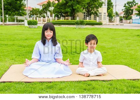 Close up of beautiful buddhist asian children sit on wooden mat praying and meditation in the garden.