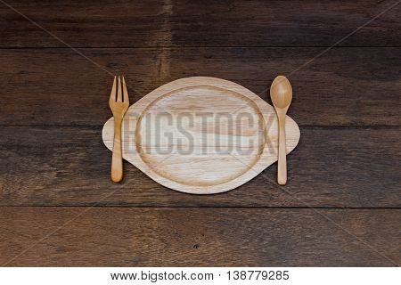 Close up of natural wooden dish with wooden spoon and fork on wood plank.