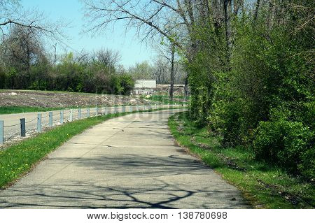 A paved bicycle trail goes through the Forest Preserve District of Will County's Joliet Iron Works Historic Site in Joliet, Illinois.