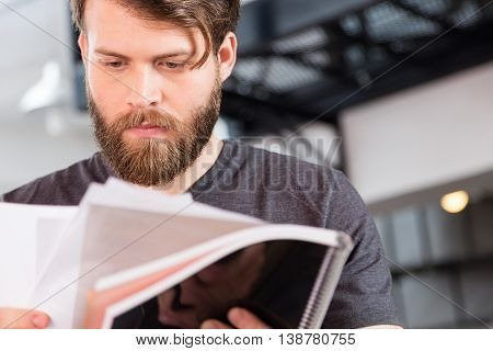 Casual bearded businessman reading document paper close up business man face modern office low angle view