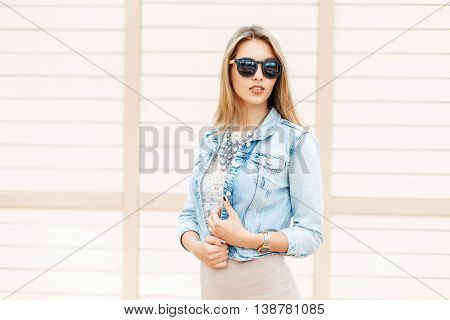 Beautiful Fashionable Woman In Sunglasses And Jeans Jacket Standing On The Beach Near The Wooden Wal