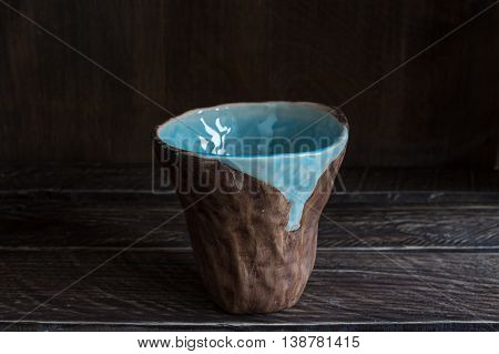 clay cup on a brown background brown-blue clay cup