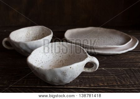 set of white pottery on a brown background white pottery in brown speckled plates and cups from clay