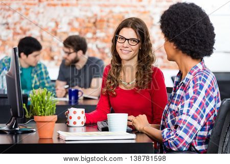 Two Women sitting working office desk computer, business people colleagues diverse mix race group businesspeople casual wear