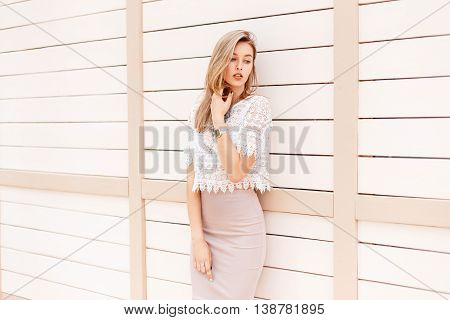 Beautiful Woman In A Summer Shirt With A Vintage Lace Stands Near A Light Wooden Wall