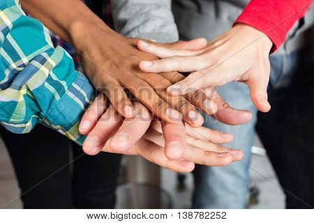 Diverse people team hands on top of each other support teamwork mix race group