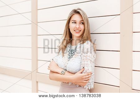 Stylish Beautiful Woman Smiling In A Lace Blouse And Dress Stands Near A White Wooden Wall.
