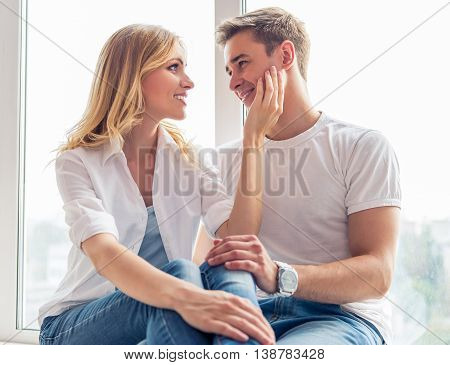 Beautiful young couple in casual clothes is looking at each other and smiling while sitting at home before the windows