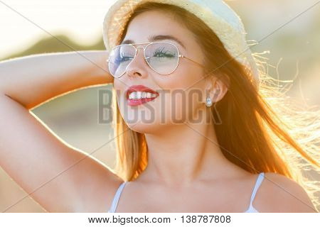 Close up face shot of attractive young woman at sunset. Backlit girl wearing hat.