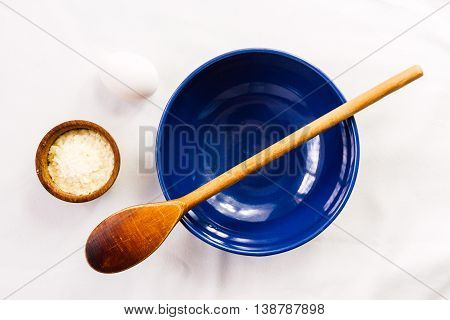 Empty blue bowl with wooden spoon eggs and dehydrated potato on white tablecloth