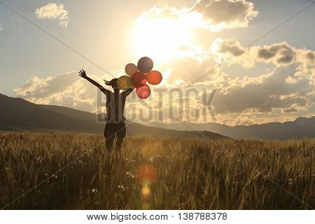 cheering young asian woman open arms on sunset grassland with colored balloons