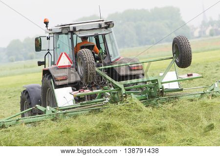 Farmer Uses Tractor To Spread Hay On The Field