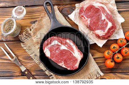 cast iron pan with raw ribeye steak on wooden background.