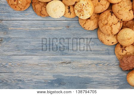 Cookies and sweet biscuits at blue wood, background with copy space. Oatmeal and chocolate drops cookies border, dessert for tea.