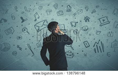 Businessman drawing a media icons on a wall