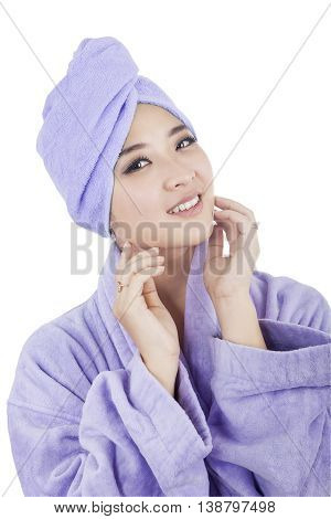 Attractive young woman wearing bathrobe with a towel on her head smiling at camera