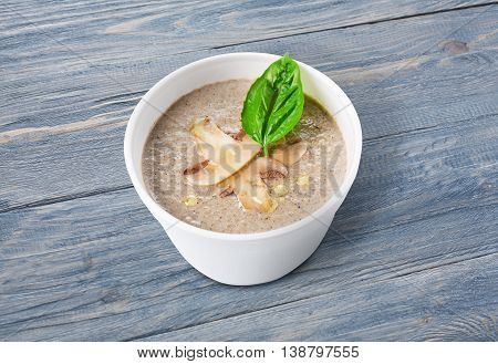 French cuisine hot food delivery - mushroom soup closeup in white plastic plate at blue wooden background, healthy eating concept