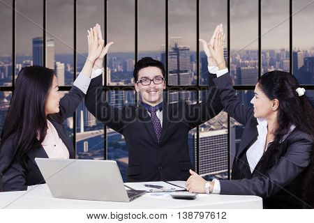Cheerful business team clapping hands together in the office to celebrate a good job