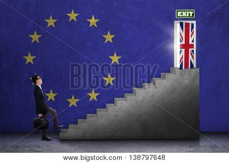 Brexit concept. Young businessman walking on the stairs toward exit door with flag of UK and EU
