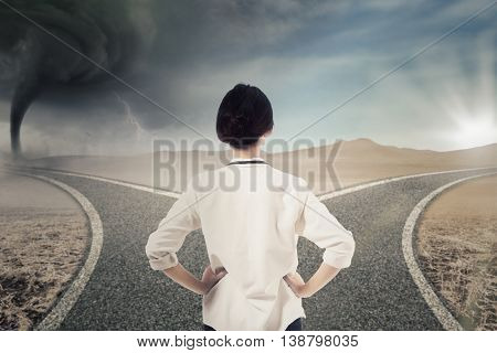 Back view of a young businesswoman looking at two highway with storm and bright sunlight