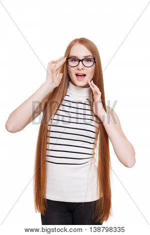Redhead long-haired woman touch her eyeglasses. Young red ginger stylish excited girl in striped blouse. Beautiful attractive female portrait isolated at white background.