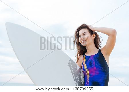 Portrait of cheerful young woman surfer in swimwear with surfboard on the beach
