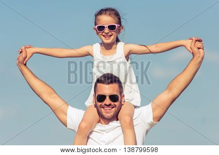 Portrait of young dad and his cute little daughter looking at camera and smiling. Girl is sitting on her father's shoulders sky on the background