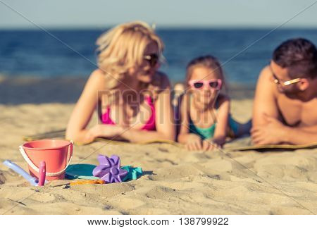 Kid's toys lying on the sand in the background beautiful young parents and their cute little daughter in swimsuits and sun glasses are lying on the sunny beach